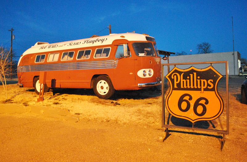 The tour bus of Bob Wills and his Texas Playboys is parked beside a historic Phillips 66 station and sign in Turkey. Texas.