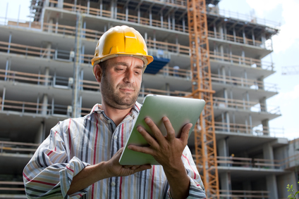 construction worker checks tablet