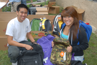 Two volunteers, Gerald and Lillian, help hand out backpacks to children.