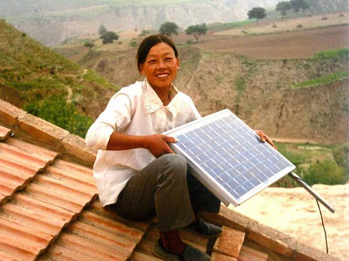A Chinese Woman Holds Up a Solar Panel