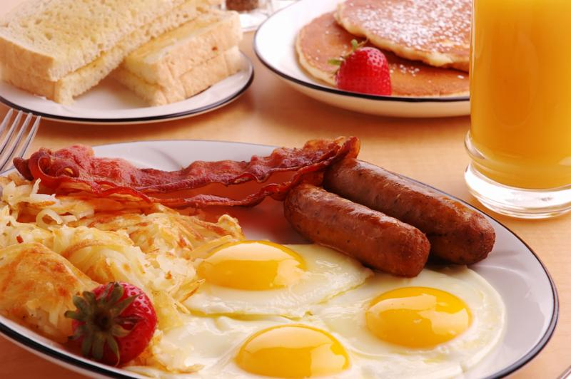 A typical American hearty breakfast with sausage eggs bacon orange juice hash browns pancakes and toast.