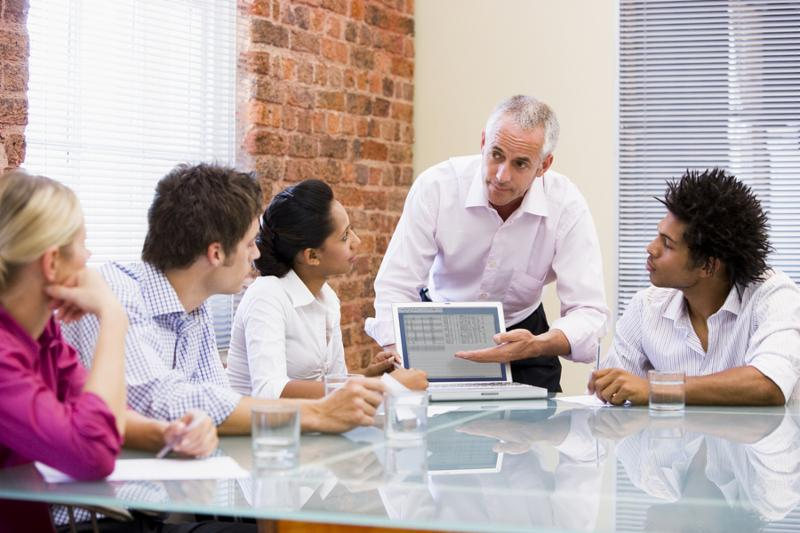 Business man giving presentation on a laptop to group of colleagues