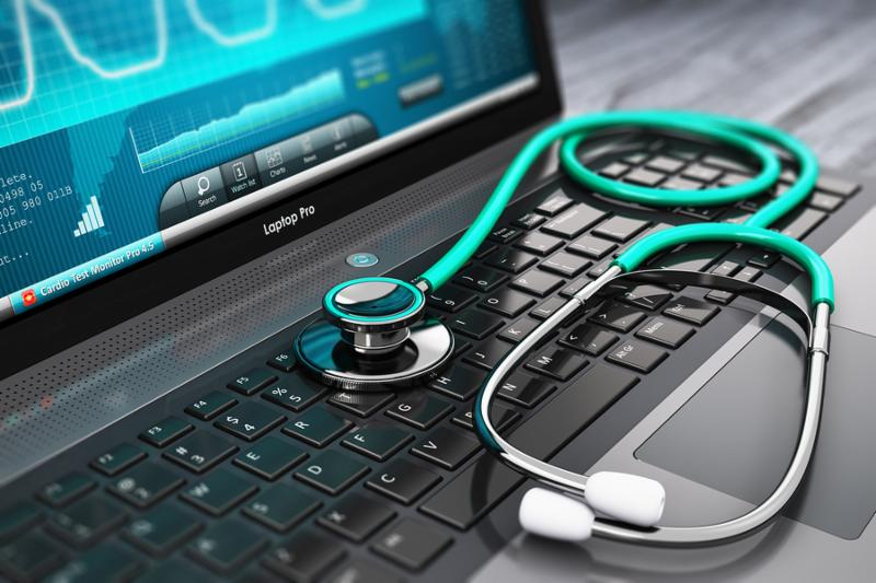Laptop or notebook computer PC with medical cardiologic diagnostic test software on screen and stethoscope on black wooden business office table with selective focus effect