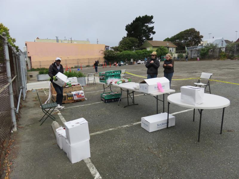volunteers setting up food and tables in a parking log