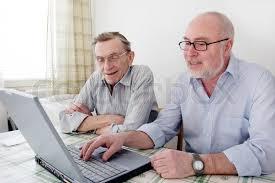 two men smiling at a laptop