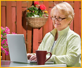 smiling woman with laptop in garden