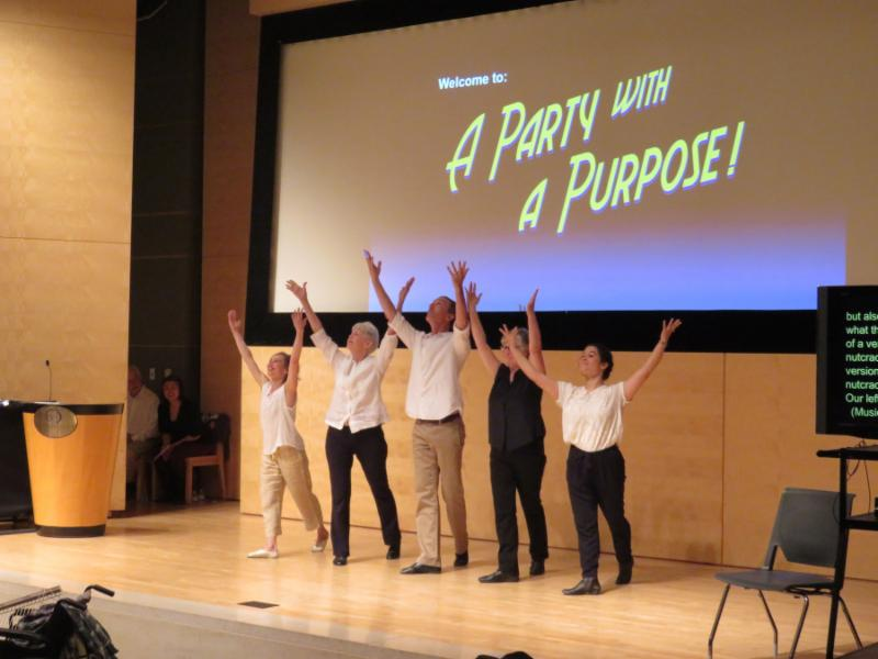 dancers in front of a large screen that says Party with a Purpose