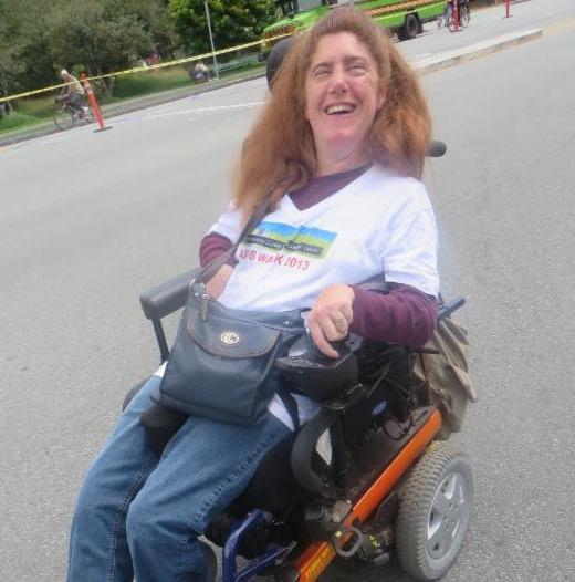 woman in wheelchair smiling at AIDS walk