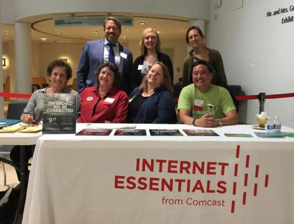 picture of people at a table with cloth that says Internet Essentials from Comcast.