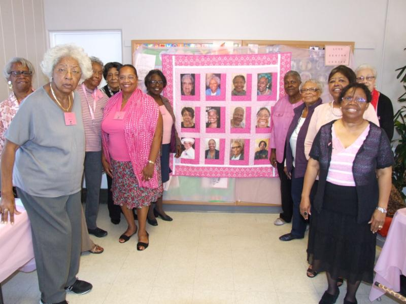 ladies in front of quilt with their picture