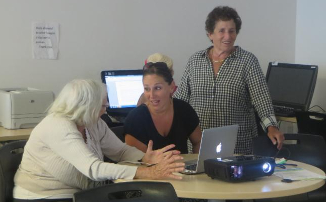 instructor with seniors at computer
