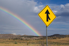 A merge sign with a rainbow in the background