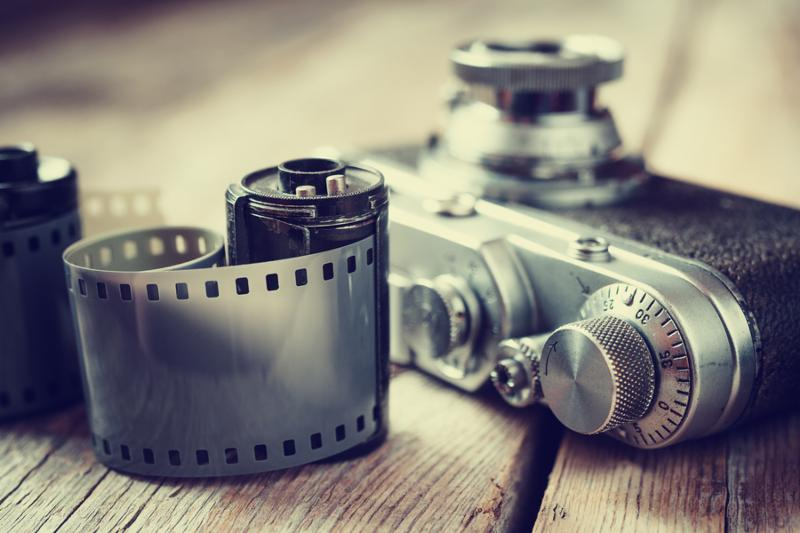 Old photo film rolls cassette and retro camera selective focus. Vintage stylized.