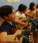 3 students playing guitar