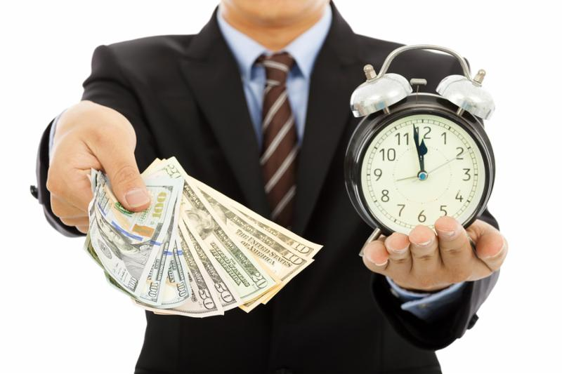 businessman holding money and clock. time is money concept     Note  Shallow depth of field