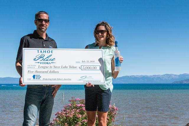 Matt Levitt_ founder_CEO of Tahoe Blue Vodka_ presents _5_000 check to Darcie Goodman Collins_ PhD_ the League_s executive director.