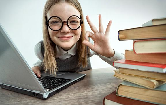 young girl with glasses sitting at desk in front of laptop next to a stack of books.