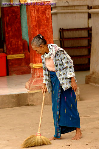 old woman sweeping