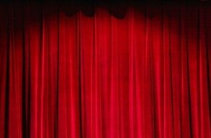Closed red velvet curtain of a theater