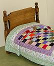 Miniature twin bed with quilt