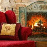 Easy chair before a lit fireplace