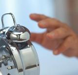 Hand reaching for an alarm clock