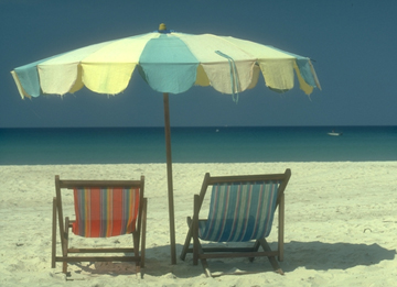 Lounge chairs and umbrella on sandy beach