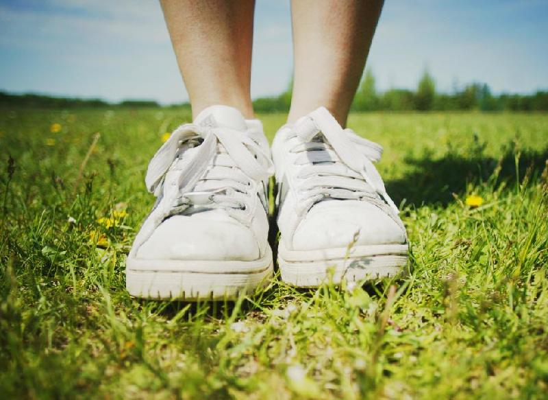Woman's bare legs, with sneakers, standing on mown grass