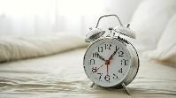 Alarm clock on an unmade bed