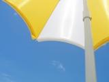 Yellow and white sunbrella against a blue sky