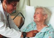 Elderly woman in hospital bed & caregiver