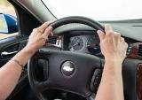 Woman's hands on a steering wheel