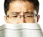 Man frowning at a newspaper