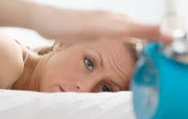 Woman in bed, turning off an alarm clock