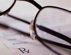 Wire-rim glasses resting on a prescription