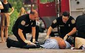 EMTs working on man lying on sidewalk