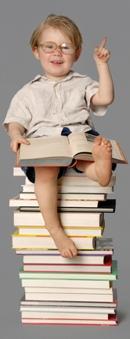 Preschool boy sitting on a tall stack of books