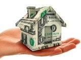 Woman's hand holding tiny house made of dollar bills
