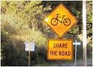 "Signpost with ""bicyclist"" and ""share the road"" signs"