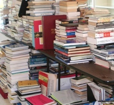 Photo of books piled on floor and table