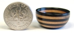 Dime, next to a smaller, turned wooden bowl