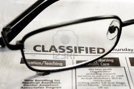 Image of a pair of magnifying glasses resting on the Classified section of a newspaper.
