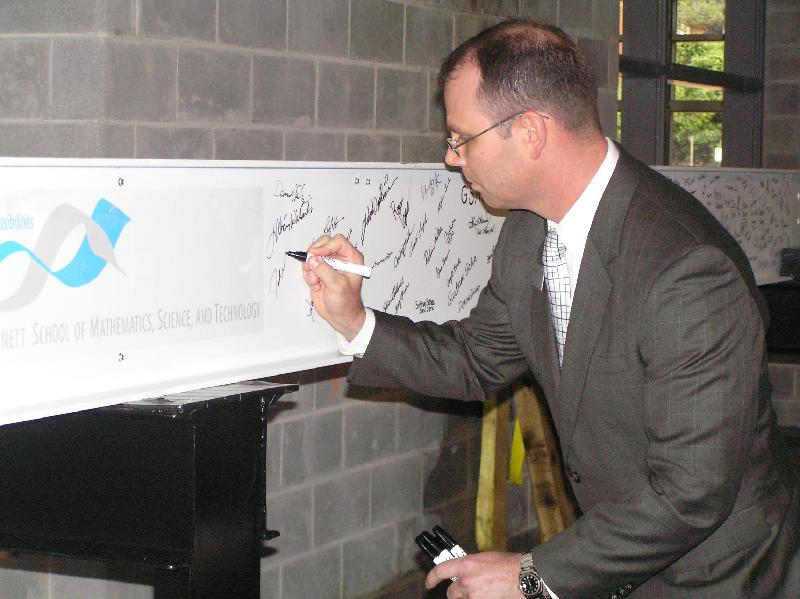 Dr. Jeff Mathews signs beam at