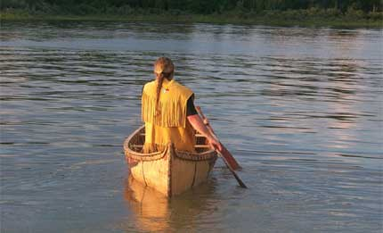 Marcel Labelle paddles a birch bark canoe