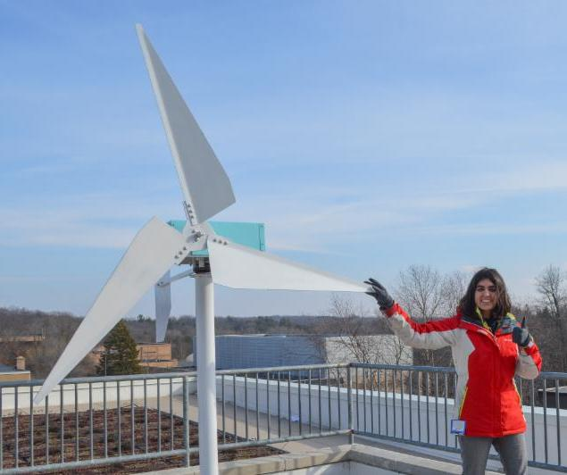 Chhavi Chaundry with wind turbine constructed from recycled parts.