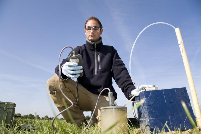 man taking soil-water measurements from the ground