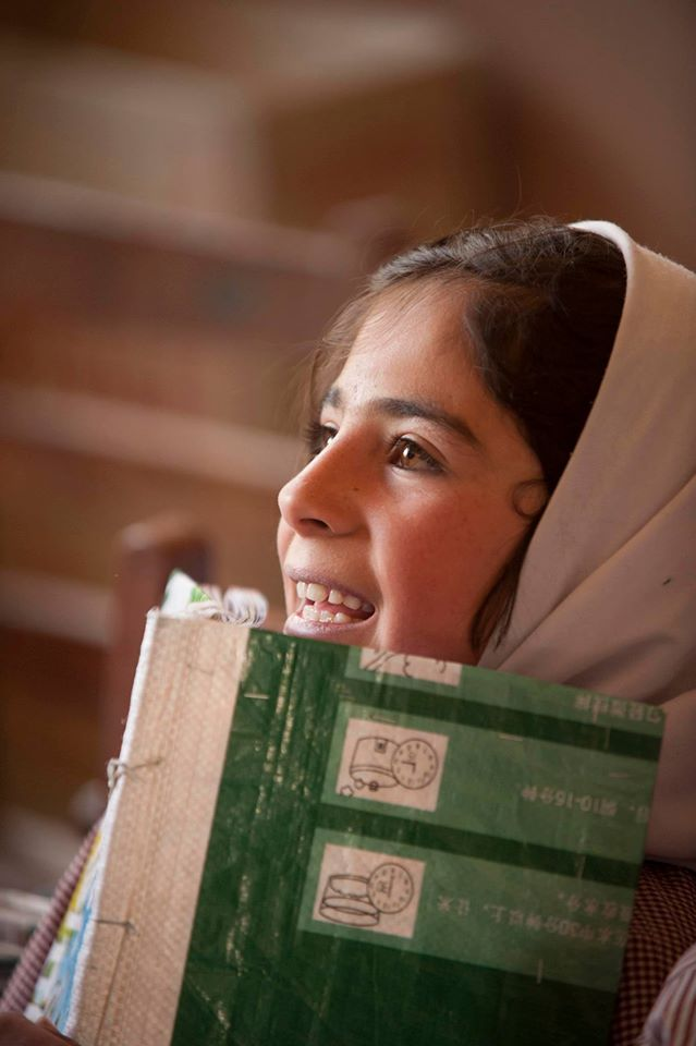 Girl smiles holding book