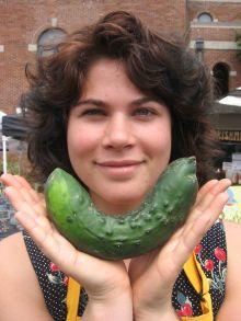 market volunteer with a cucumber