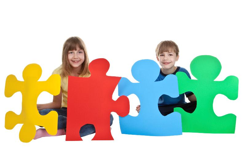 two children sitting and hold different color pieces of puzzle