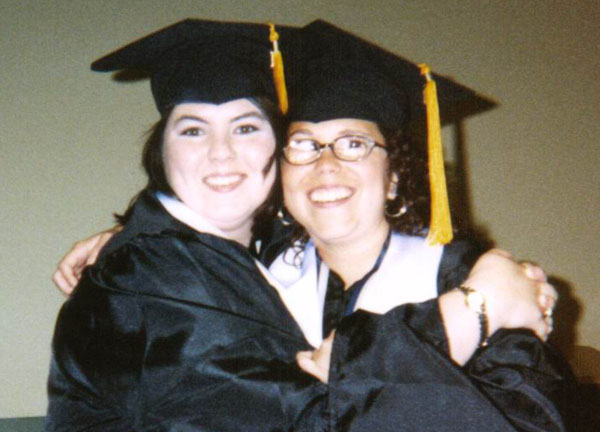 Julia poses with a friend in her graduation outfit